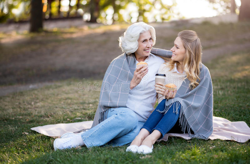 Two cheerful smiling women sitting on the ground and talking. Outdoors conversation. Beautiful pleasant daughter and mother talking an eating cakes while royalty free stock photography