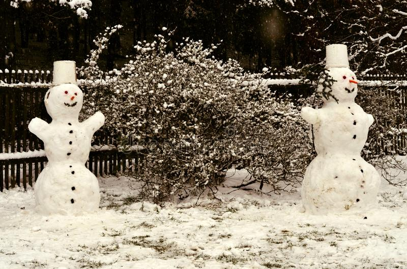 Two cheerful snowmen standing in the garden stock photos