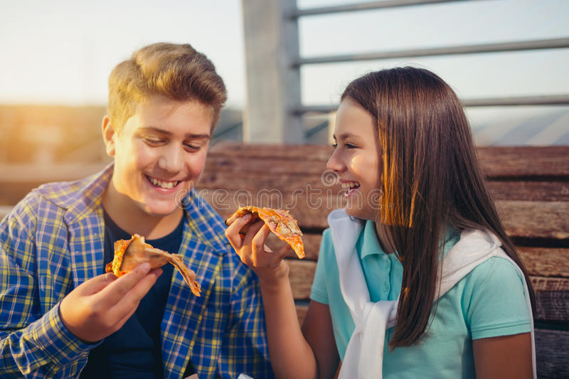 Two cheerful teenagers, girl and boy, eating pizza royalty free stock image