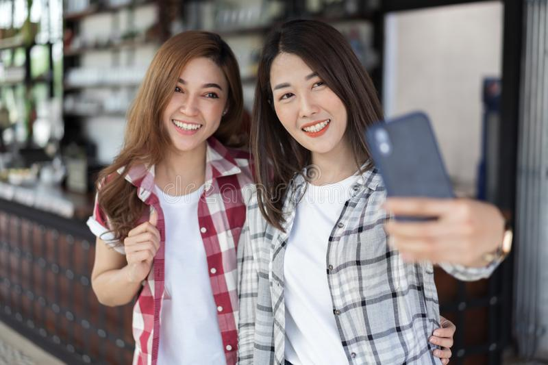 Two cheerful woman taking selfie on smartphone. Two cheerful women taking selfie on a smartphone royalty free stock image