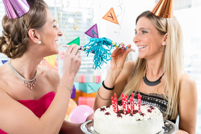 Two cheerful women and best friends holding a birthday cake royalty free stock photo