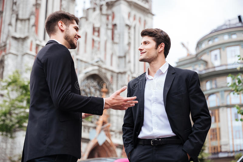 Two cheerful young businessmen standing and talking royalty free stock photos