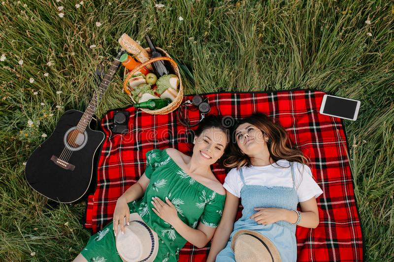 Two cheerful young fashionable women lying down on the picnic blanket and relaxing. stock photos
