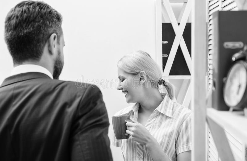Two cheerful young people holding coffee cups and talking while standing in office. Two casual people. Job interview. Two cheerful young people holding coffee stock photography