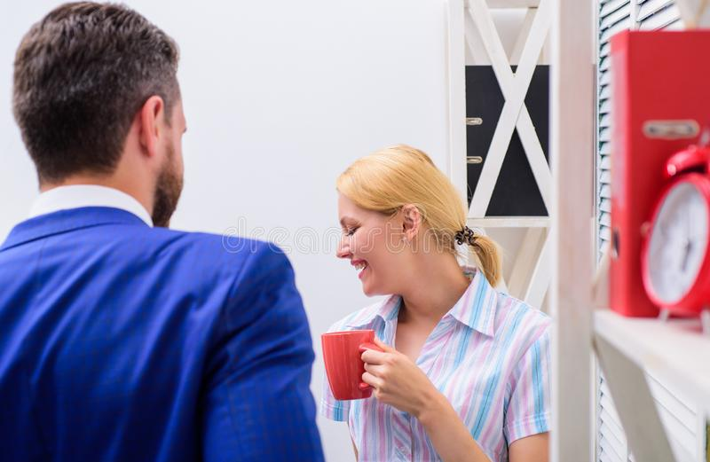 Two cheerful young people holding coffee cups and talking while standing in office. Two casual people. Job interview. Two cheerful young people holding coffee stock image