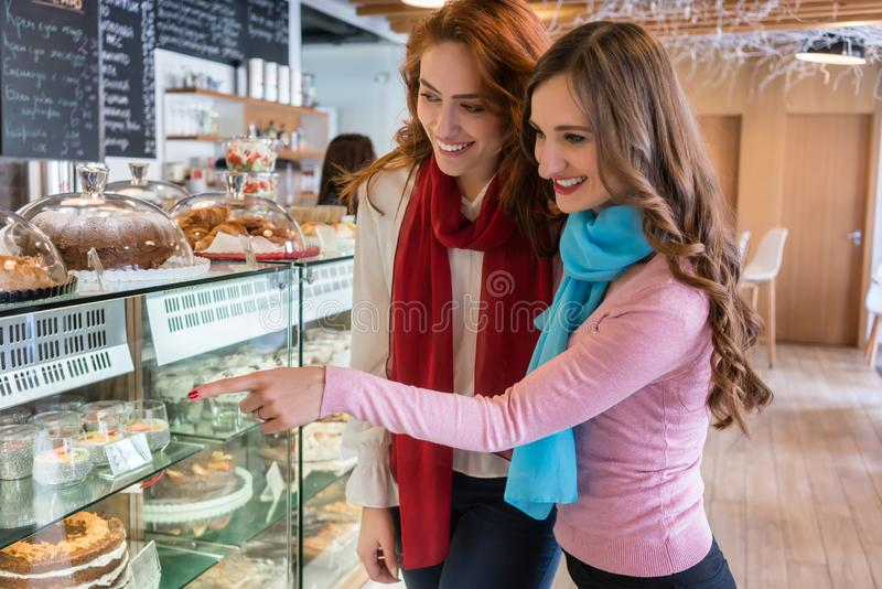 Two cheerful young women in front of the showcase of a modern ca. Side view of two cheerful young women and best friends smiling in front of the showcase of a royalty free stock photo