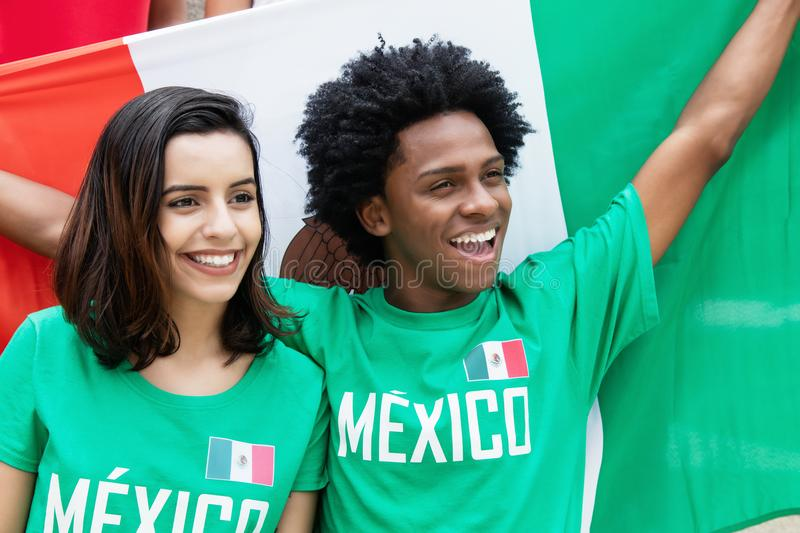 Two cheering soccer fans from Mexico at stadium. With mexican flag royalty free stock photography