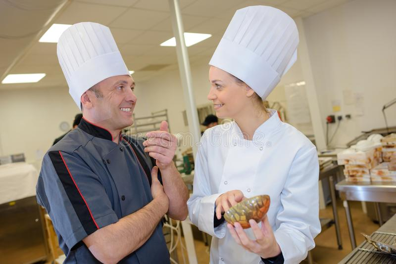 Two chefs laughing at work stock images