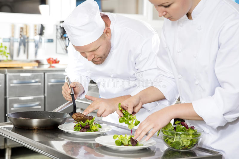 Two chefs prepares steak dish at gourmet restaurant. Professional chefs prepares beef meat dish in a professional kitchen at gourmet restaurant or hotel royalty free stock images