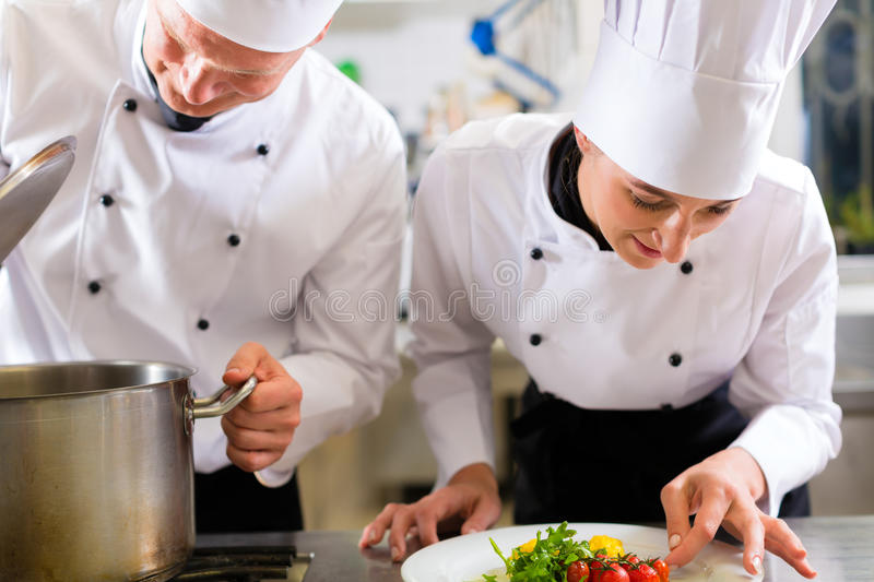 Two chefs in team in hotel or restaurant kitchen stock image