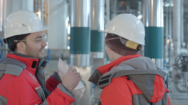 Two chemical factory workers having conversation in plant. stock image