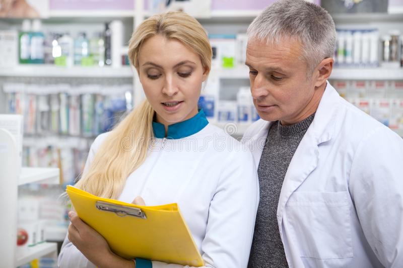 Two chemists working at drugstore together. Drugstore workers doing paperwork, checking stock in an aisle. Mature male pharmacist and his female colleague stock photography