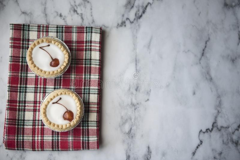 Two cherry bakewell tarts on a red cloth. With copy space stock photos
