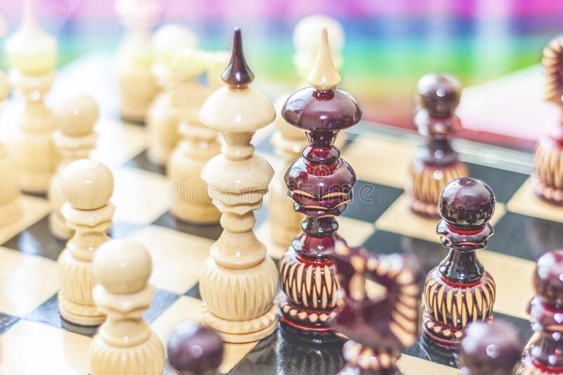 Two chess pieces of kings on a wooden chessboard surrounded by other pieces on a rainbow background. The concept of same-sex love royalty free stock photo