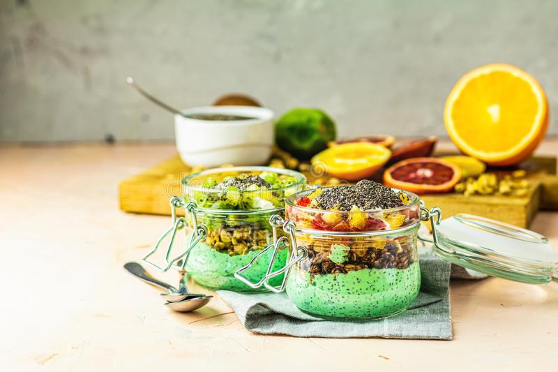Two chia seed pudding with matcha green tea, kiwi and granola, orange in glasses royalty free stock photography