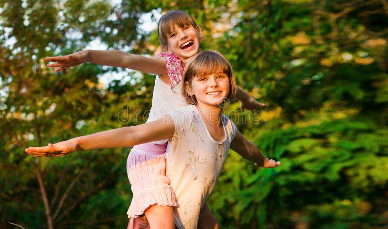 Two child girls playing together. Sisters play Superhero. Happy kids having fun, smiling and hugging. Family holiday royalty free stock image