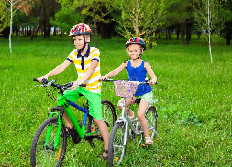 Two children on bicycles in a field of grass stock image
