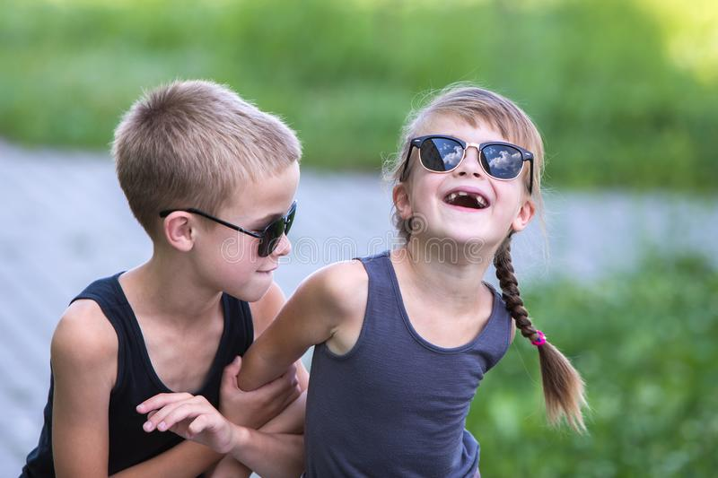 Two children in black sunglasses having fun time outdoors in summer royalty free stock photo