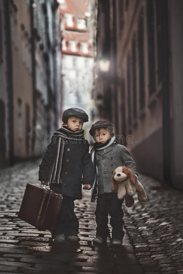 Two children, boy brothers, carrying suitcase and dog toy, travel in the city alone. At night stock images
