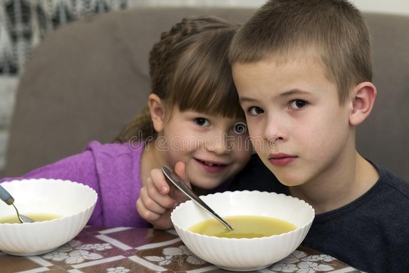 Two children boy and girl eating soup stock photography