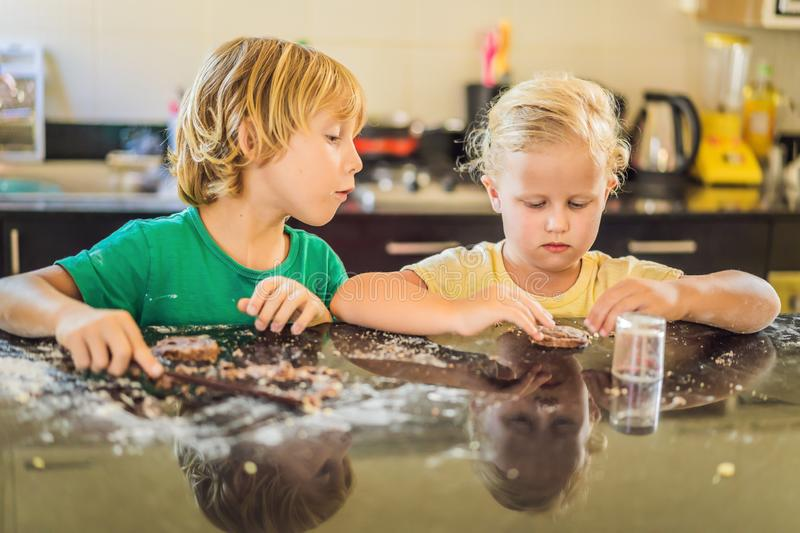 Two children a boy and a girl make cookies from dough stock images
