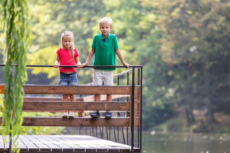 Two children boy and girl standing on wooden deck on a lake shore stock photo