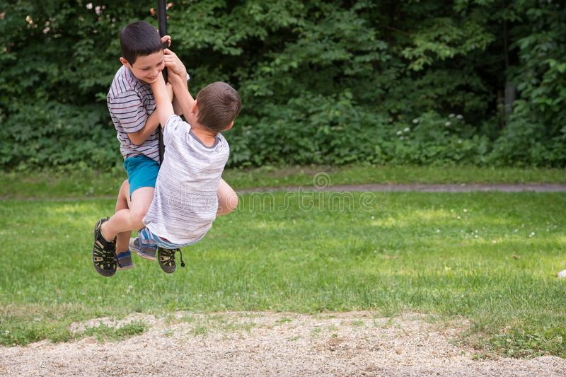 Children playing in park on zip line swing royalty free stock photo