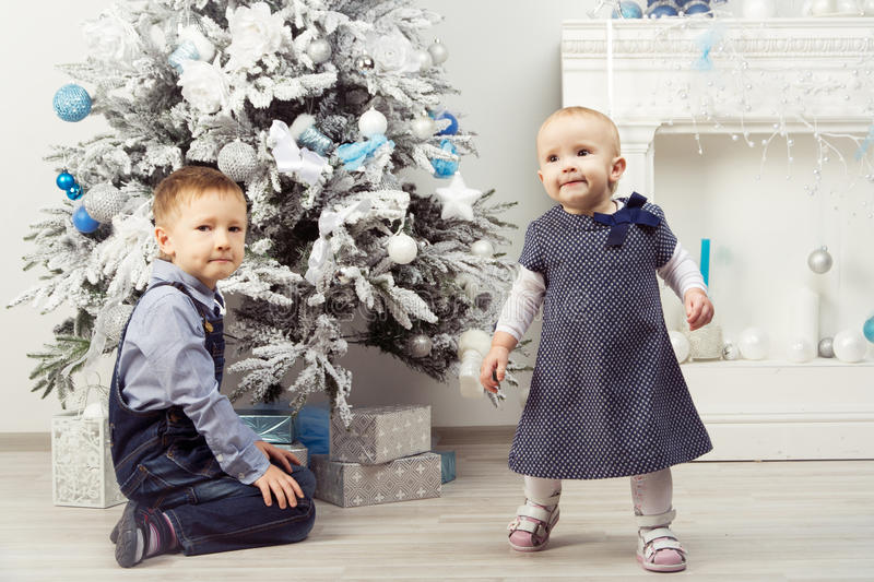 Two children (brother and sister) near christmas tree. Boy sitting under tree. Girl walking out of frame royalty free stock images