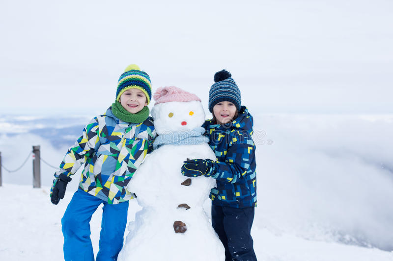 Two children, building snowman on top of mountain stock image