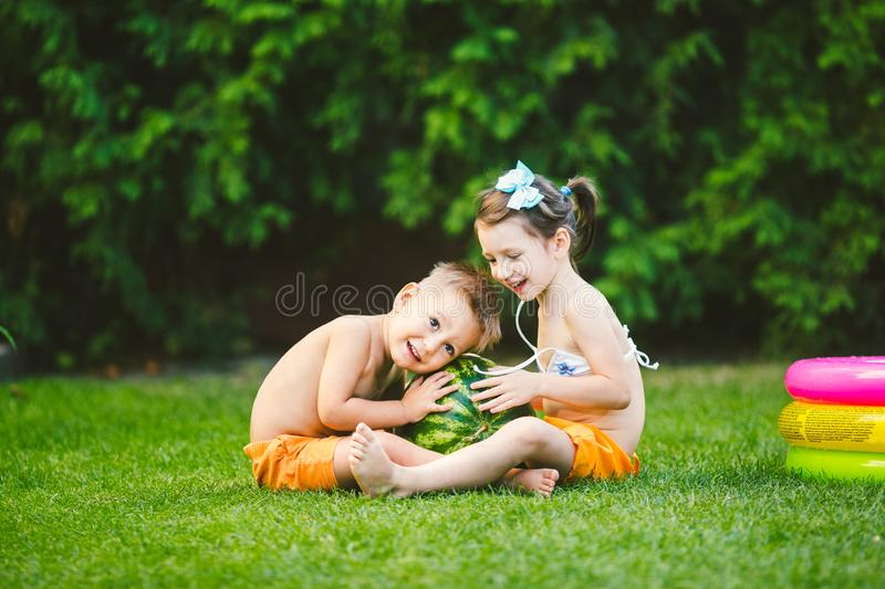 Two children, Caucasian brother and sister, sitting on green grass in backyard of house and hugging big tasty sweet watermelon royalty free stock images