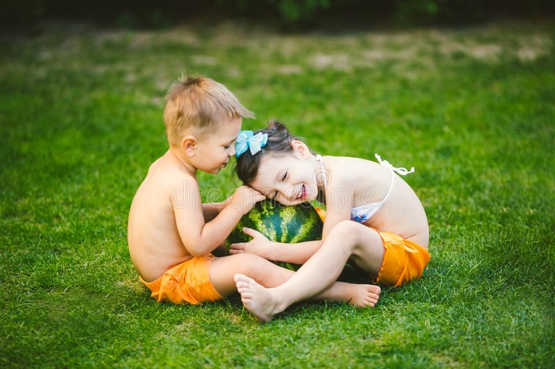 Two children, Caucasian brother and sister, sitting on green grass in backyard of house and hugging big tasty sweet watermelon royalty free stock image