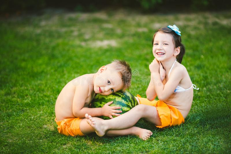 Two children, Caucasian brother and sister, sitting on green grass in backyard of house and hugging big tasty sweet watermelon stock photo