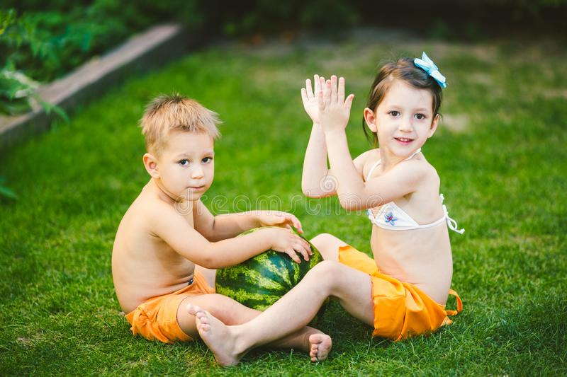 Two children, Caucasian brother and sister, sitting on green grass in backyard of house and hugging big tasty sweet watermelon stock photos