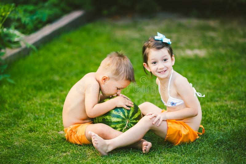 Two children, Caucasian brother and sister, sitting on green grass in backyard of house and hugging big tasty sweet watermelon royalty free stock photography