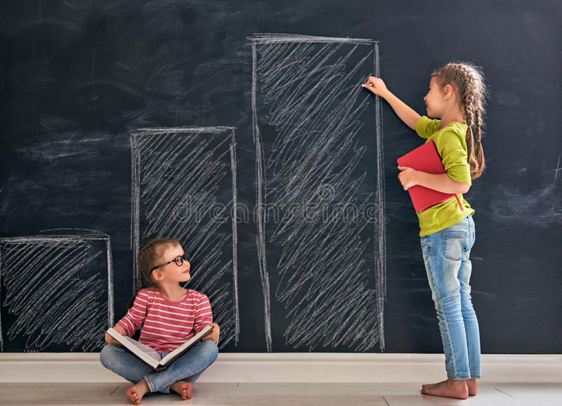 Two children in the class. Back to school! Two happy cute industrious children indoors. Kid is drawing graphs on blackboard in the class. Girl reading a book stock images