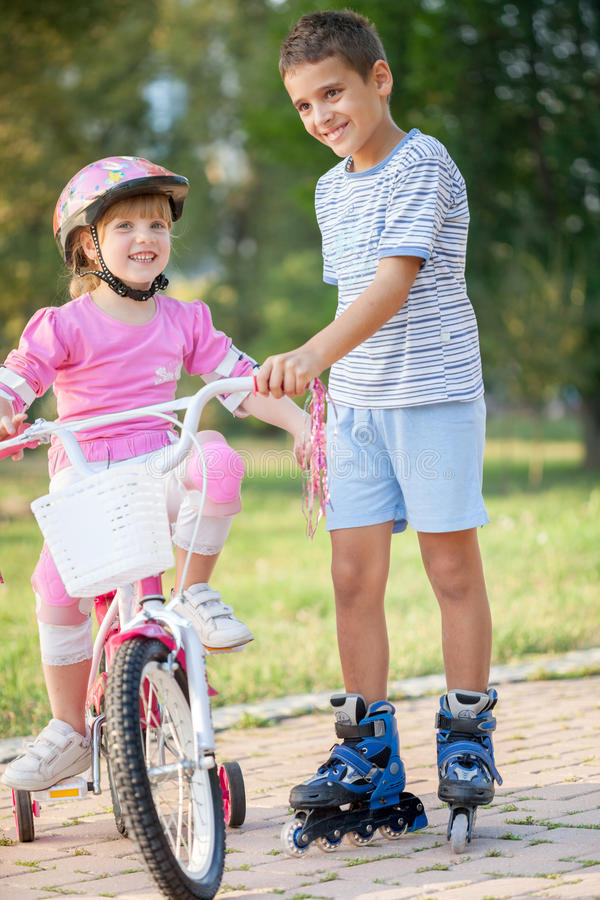 Two Children On Cycle Ride In Countryside. Brother and sister outdoors riding bikes and roller royalty free stock image