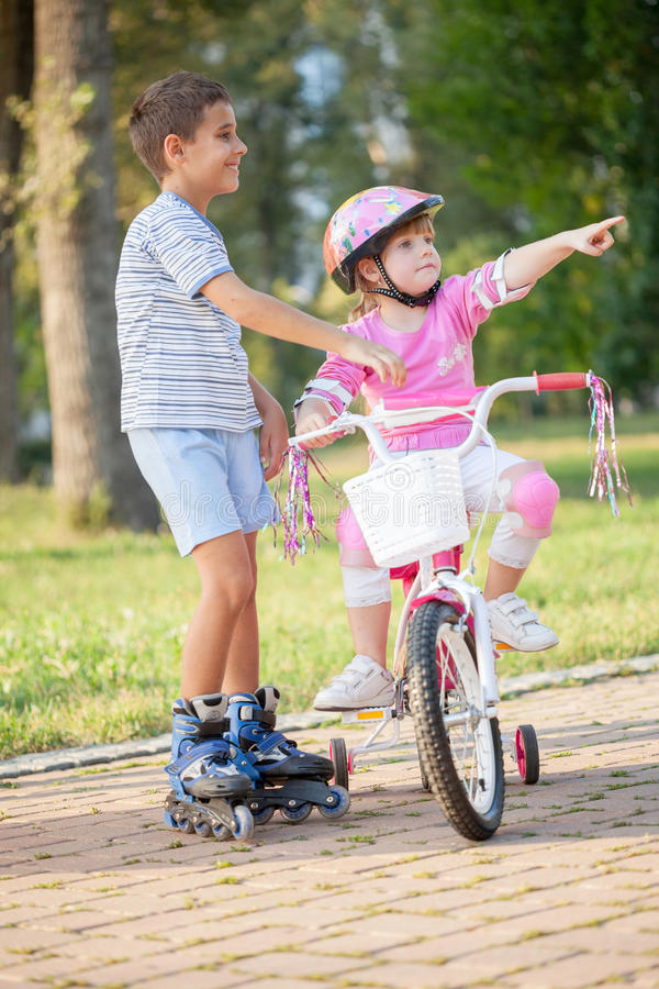 Two Children On Cycle Ride In Countryside. Brother and sister outdoors riding bikes and roller in park stock images