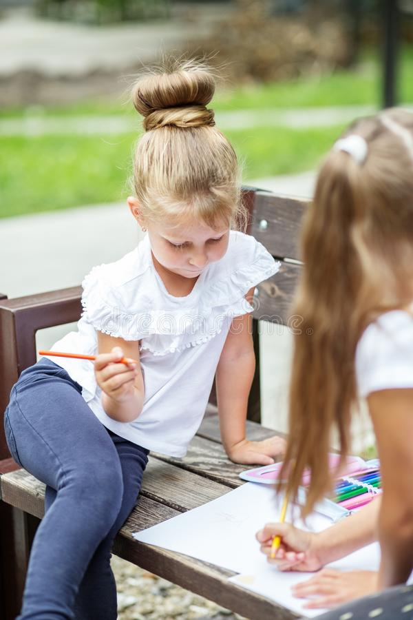 Two children draw with pencils in a school park. The concept of school, friendship, drawing, study, hobby.  stock photo