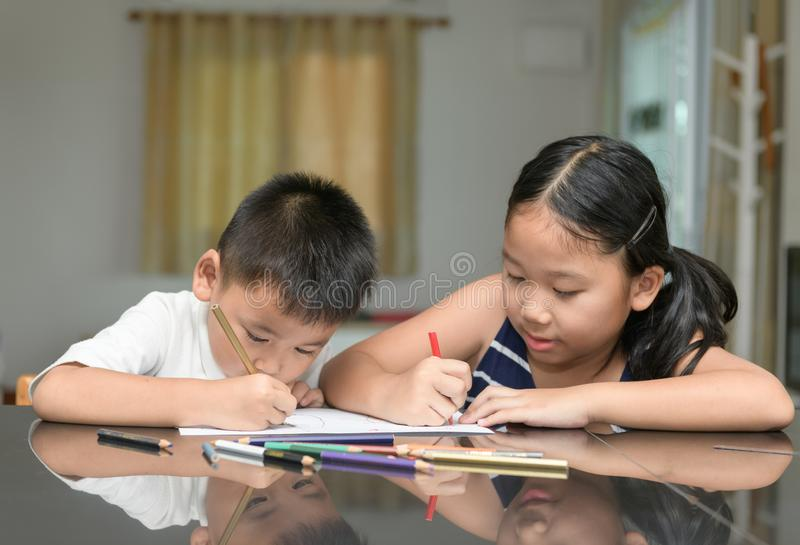 Two children are drawing together stock photo