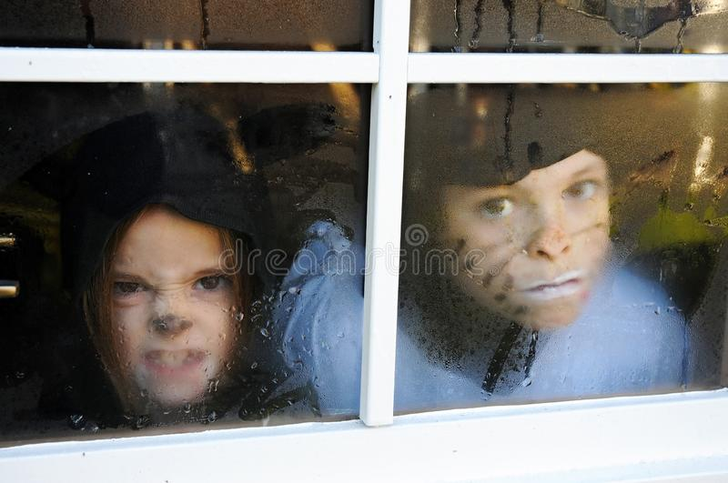 Children behind a window with raindrops royalty free stock photography