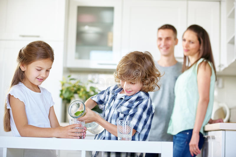 Two children drinking water with fresh lime. In the kitchen while parents are watching royalty free stock photos