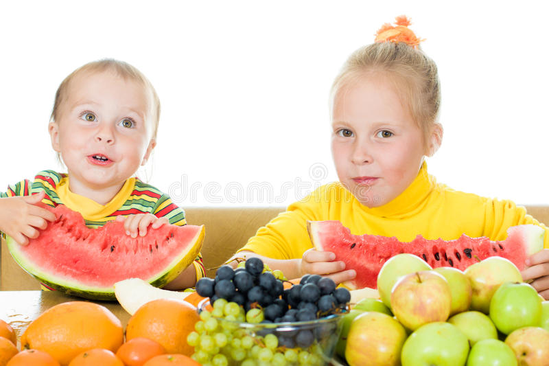 Two children eat fruit at a table royalty free stock photo