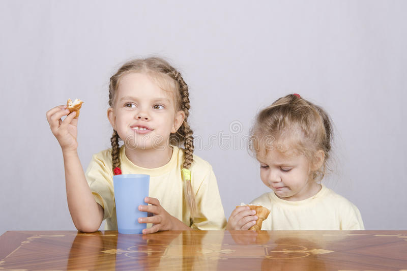 Two children eat a muffin at the table