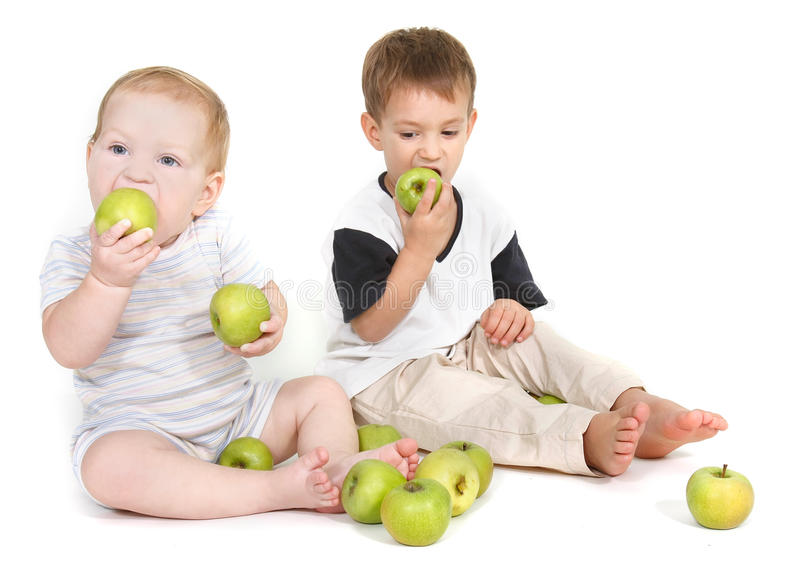 Two children eating green apples royalty free stock images