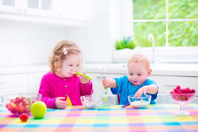 Two children eating yoghurt royalty free stock images