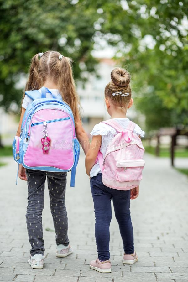 Two children go to school with backpacks. The concept of school, study, education, friendship, childhood. Two children go to school with backpacks. The concept stock photo