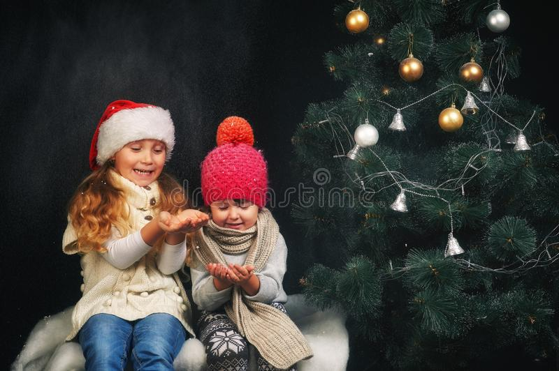 Two children in hats and warm sweaters on Christmas eve. Girls having fun by the Christmas tree . two children in hats and warm sweaters on Christmas eve royalty free stock images