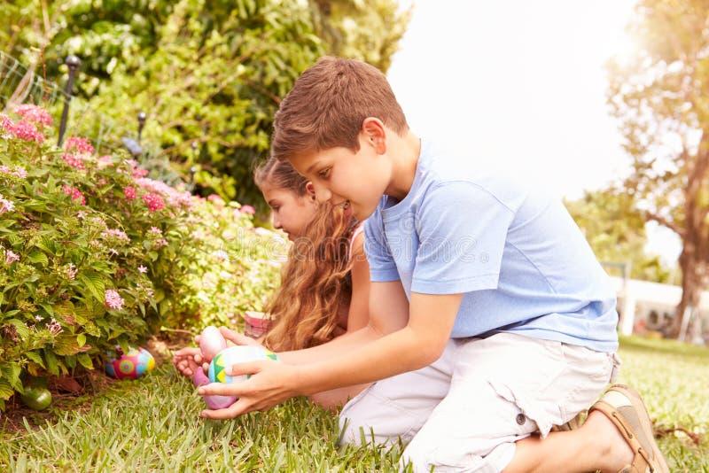 Two Children Having Easter Egg Hunt In Garden stock images