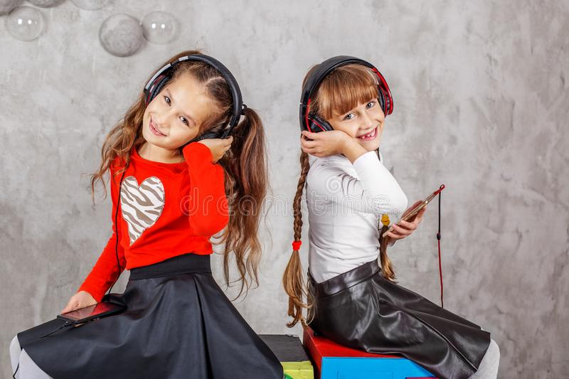 Two children in the headphones listen to music. Concept music, r. Adio, dance, life stroke, rest stock image