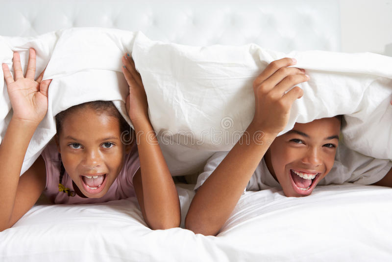 Download Two Children Hiding Under Duvet In Bed Stock Image - Image: 31164149